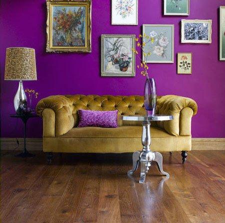 Una parete di un viola squillante smorzato e valorizzato da tanti piccoli quadretti e dal divano senape.