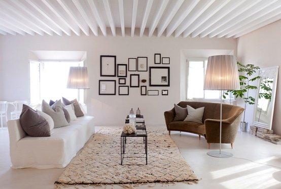 Il salotto di un b&b. Le piantane sembrano delle grandi abatjours; sullo sfondo tante cornici di dimensioni diverse creano un grande quadro.