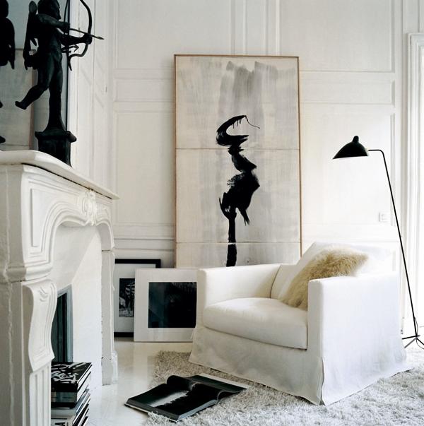 Una casa bianca e nera..il caminetto come porta riviste, i quadri semplicemente appoggiati: un angolo relax.