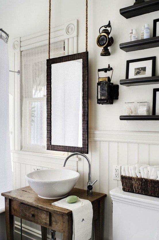 Bellissimo lo specchio sospeso e il lavabo poggiato sulla toilette il legno..
