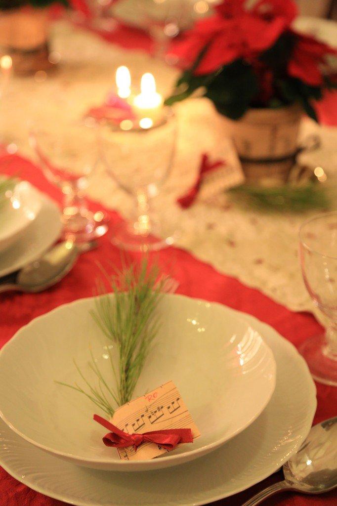 I segnaposto, fatti da un rametto di pino, un nastrino e il nome scritto sullo spartito.