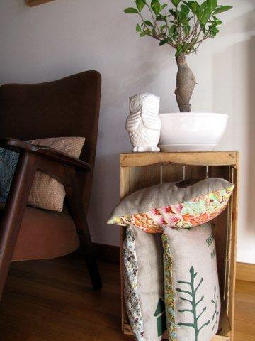 Una cassetta della frutta vintage contiene i bellissimi cuscini fatti da Aina.