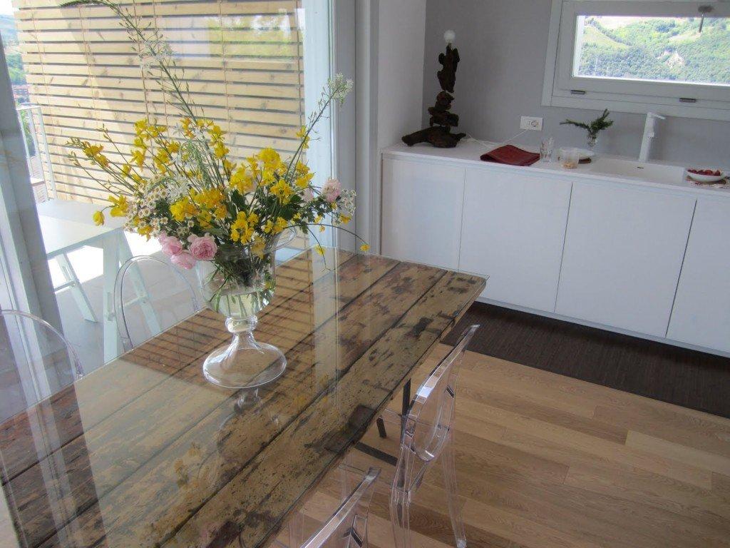 Una cucina realizzata da Martino design:  la zona cottura luminosa e minimale, scaldata dal parquet e dal tavolo da pranzo, realizzato riciclando una vecchia porta in legno.