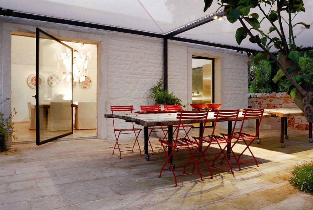 La zona pranzo esterna. I tavoli sono realizzati con antiche porte.